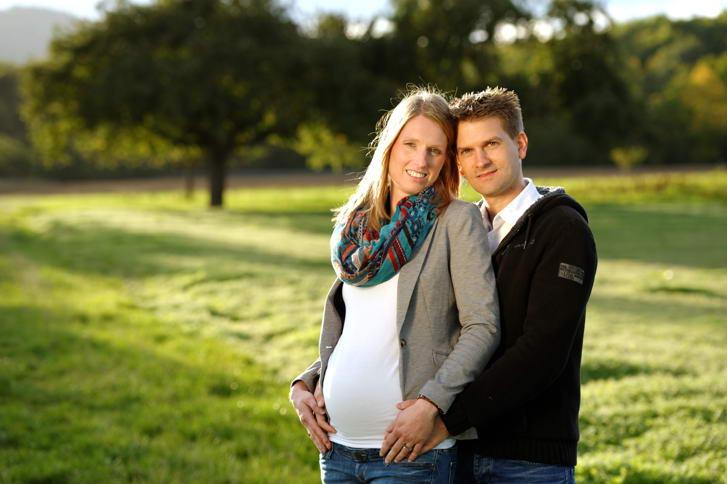 Schwangerschafts-Fotografie: stimmungsvolles Paarbild mit Babybauch im Abendlicht