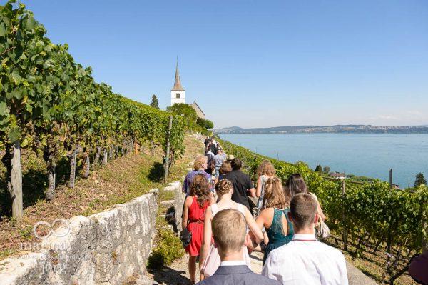 Marina und Joerg, Hochzeitsfotografen aus Giessen: Hochzeits-Gesellschaft auf dem Weg zur Kirche Ligerz am Bielersee