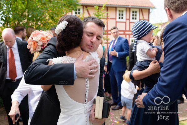 Marina und Joerg, Hochzeitsfotografen Giessen: Gratulation der Gaeste vor der Marien-Kirche Wehrshausen bei Marburg